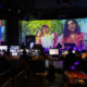 Produzent:innen sitzen vor einer Vielzahl an Bildschirme vor eine Großen Leinwand im Rahmen der Produktion der Most Wanted: Music Konferenz 2020