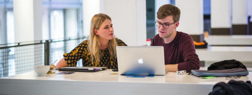 eine Frau und ein Mann sitzen nebeneinander an einem Tisch und schauen auf einen Laptop