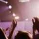 Jubelnd in die Luft gestreckte Hände, im Hintergrund helle Lichter einer Bühne