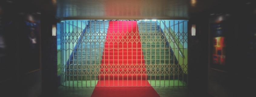 Eisengitter verschließt den Zugang zu einer mit rotem Teppich bedeckten Treppe.