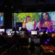 Produktionssituation der Music Business Konfernez Most Wanted: Music. Viele kleine Bildschirme vor einer großen Leinwand, auf der drei Frauen in bunter Kleidung zu sehen sind.