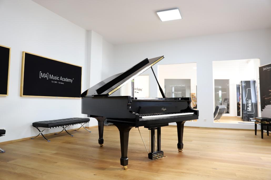 """aufgeklappter Flügel in einem Lichtdurchfluteten Raum, im Hintergrund eine Tafel mit der Aufschrift """"MA Music Academy"""""""